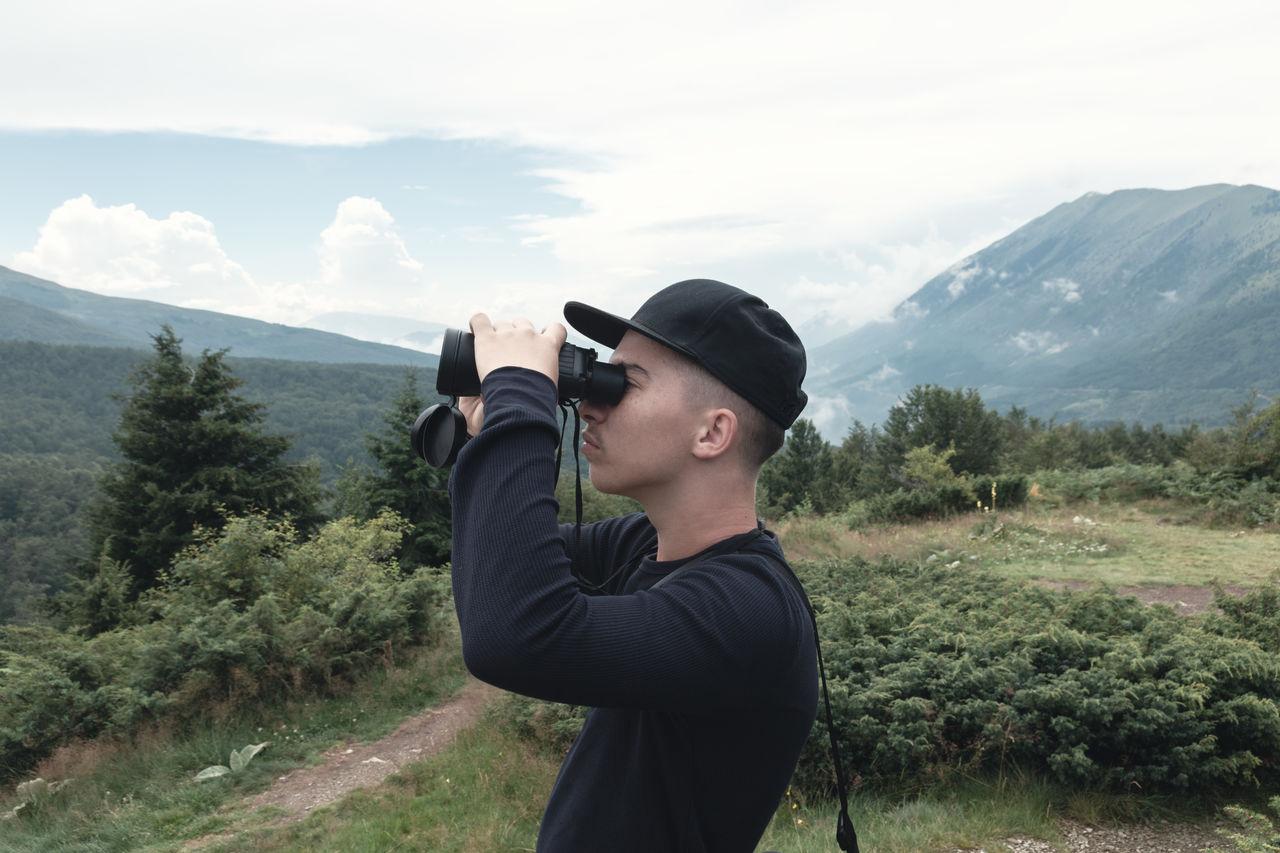 Side View Of Teenage Boy Looking Through Binoculars On Land