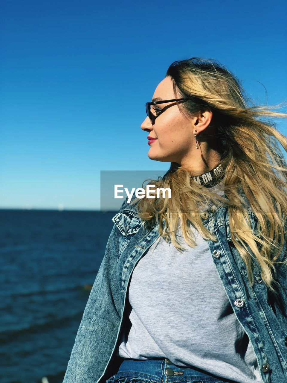 glasses, one person, lifestyles, real people, hair, sky, water, leisure activity, long hair, young adult, young women, hairstyle, eyeglasses, blue, casual clothing, sea, clear sky, standing, looking, fashion, outdoors, beautiful woman