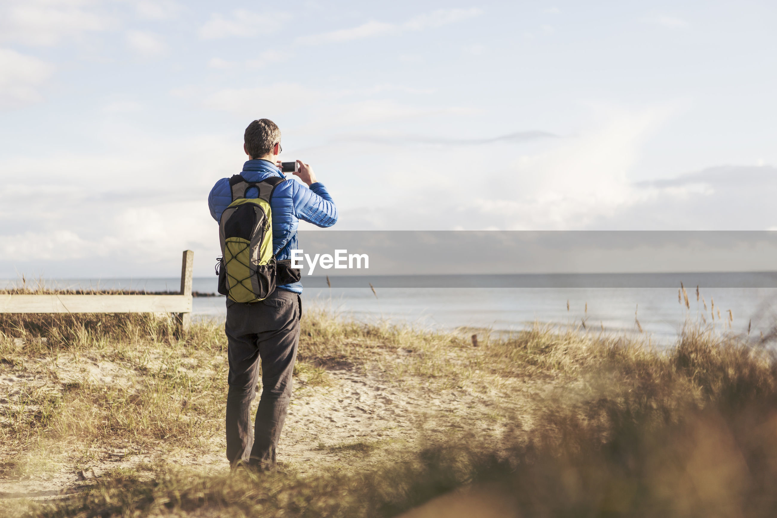 REAR VIEW OF MAN STANDING ON SHORE