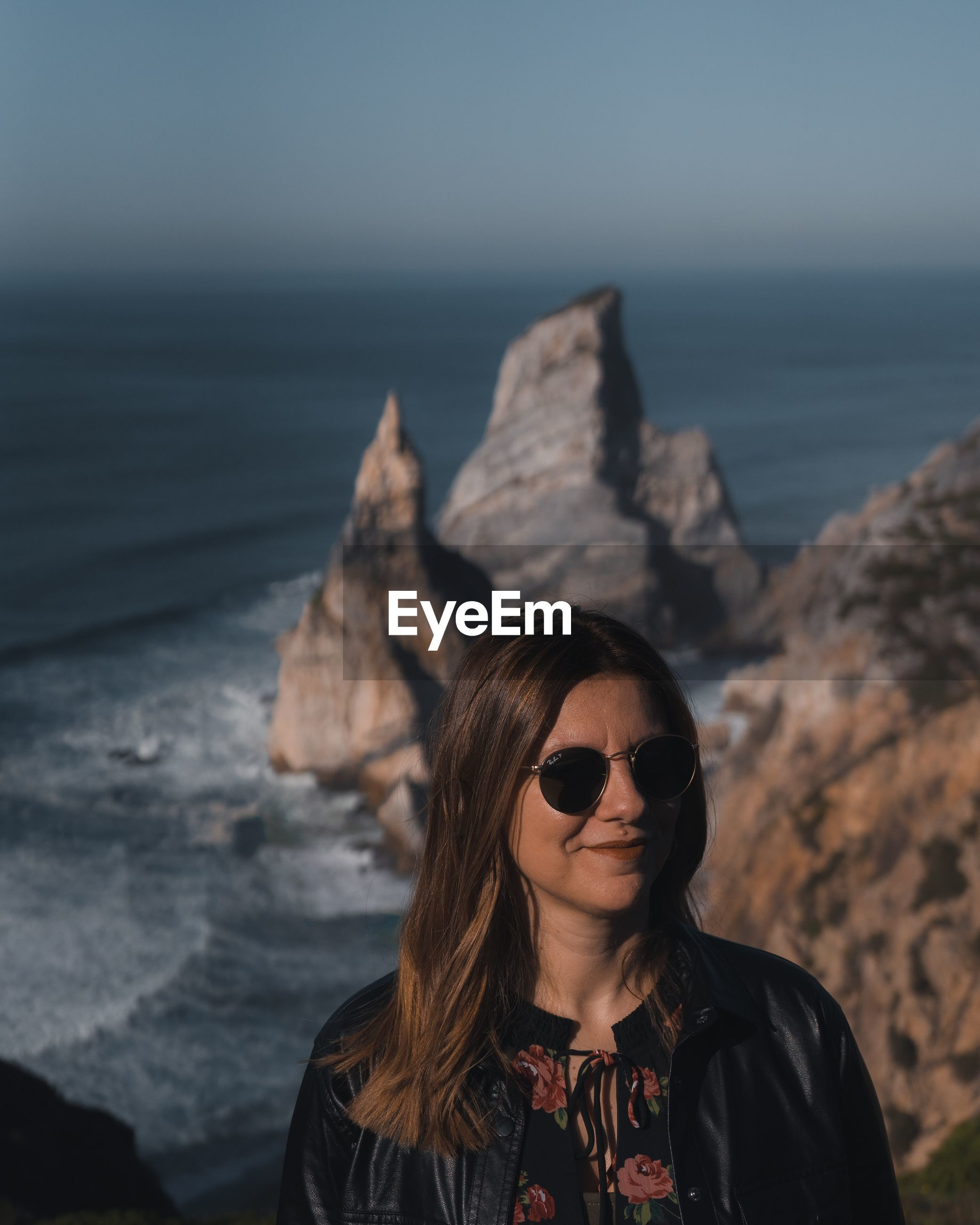 PORTRAIT OF YOUNG WOMAN WEARING SUNGLASSES ON ROCK AT SHORE