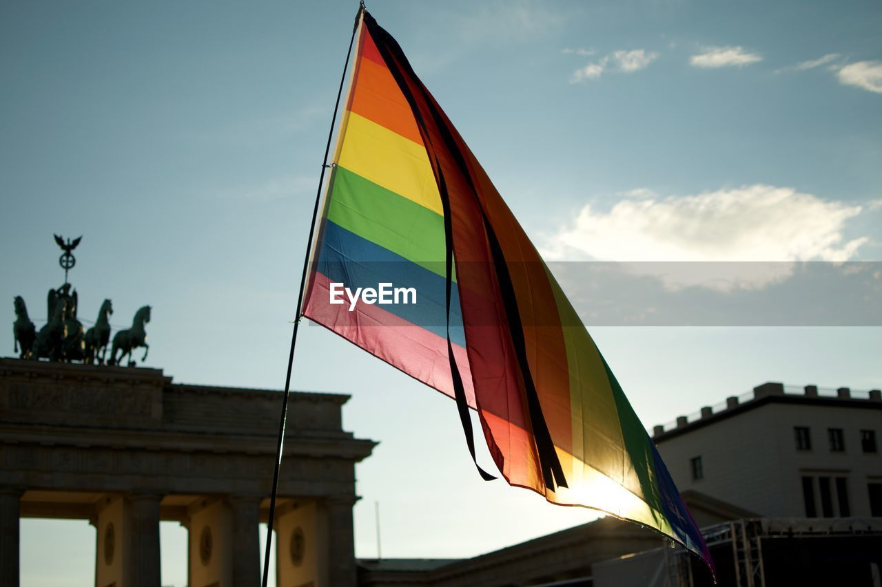 Low angle view of rainbow flag at brandeburger gate in berlin
