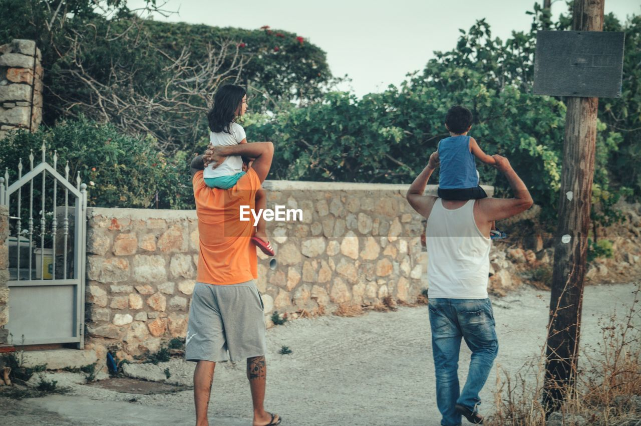 Rear View Of Men Carrying Children On Shoulder While Walking On Walkway