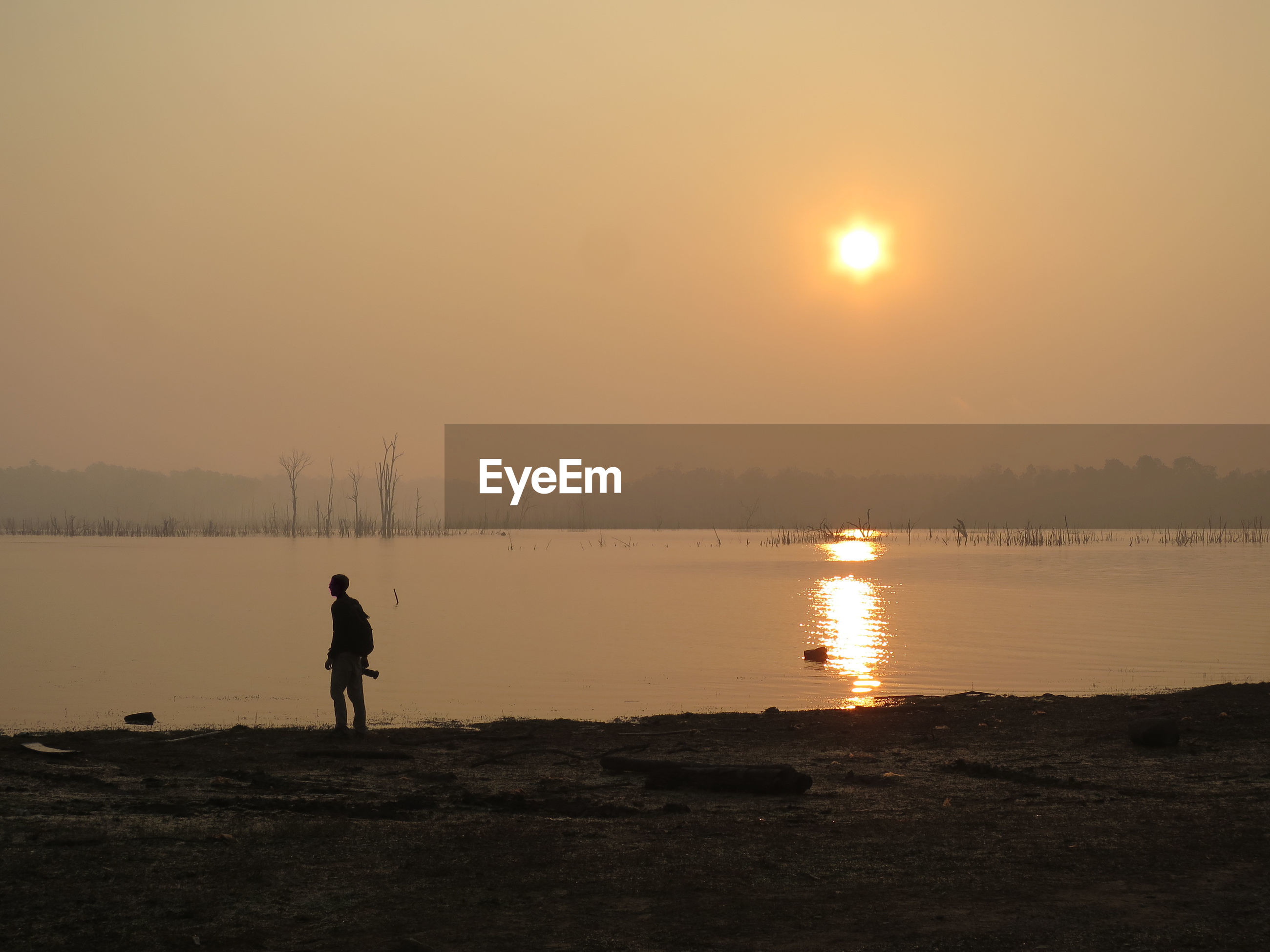 Silhouette man looking away while standing by river during sunset against sky