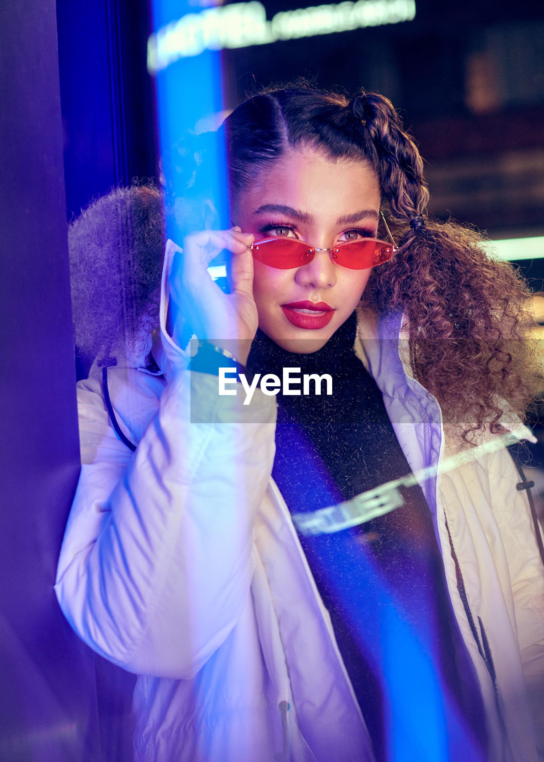 Smiling woman wearing eyewear while standing outdoors at night