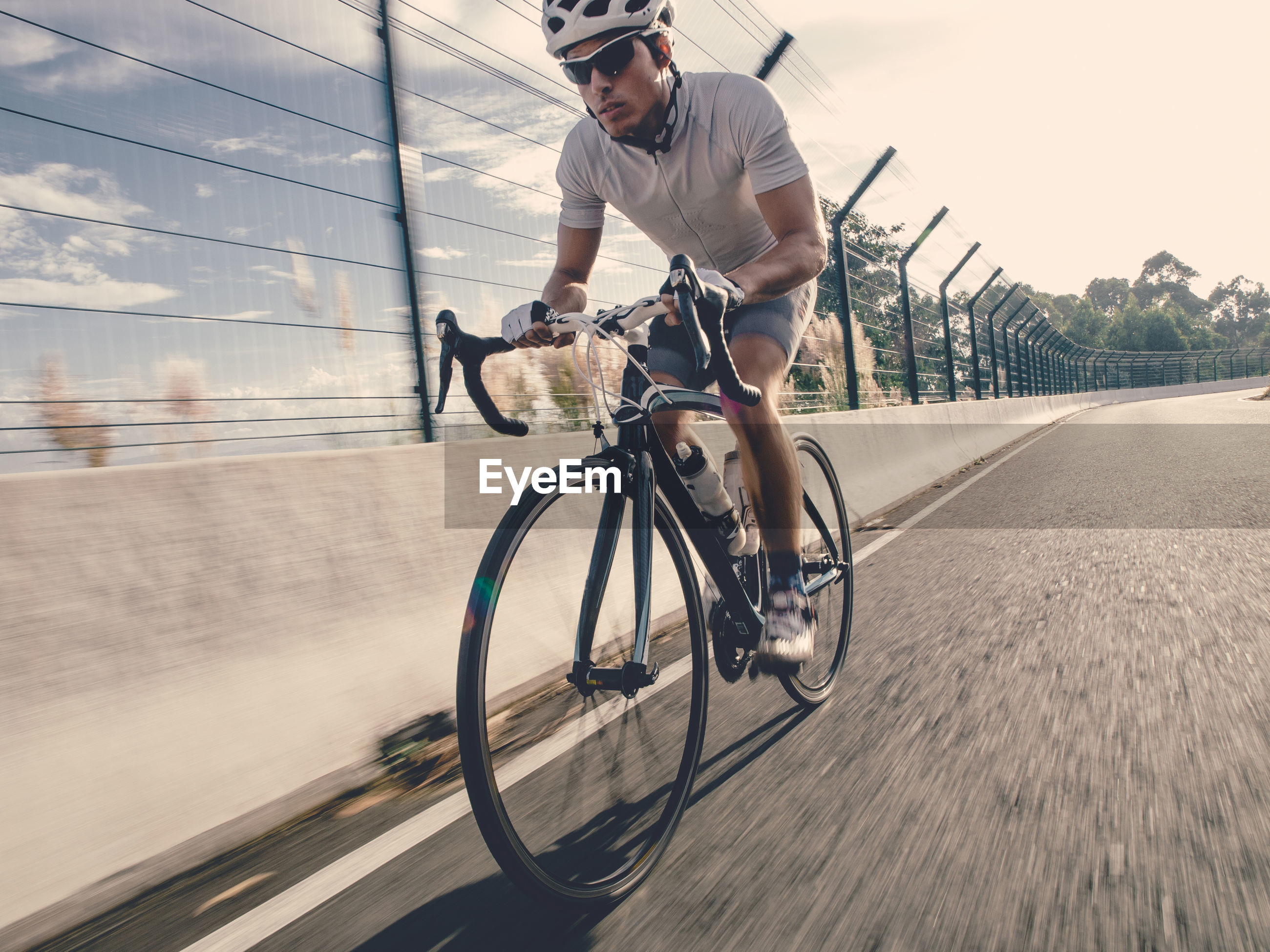 Full length of man riding bicycle on road by railing