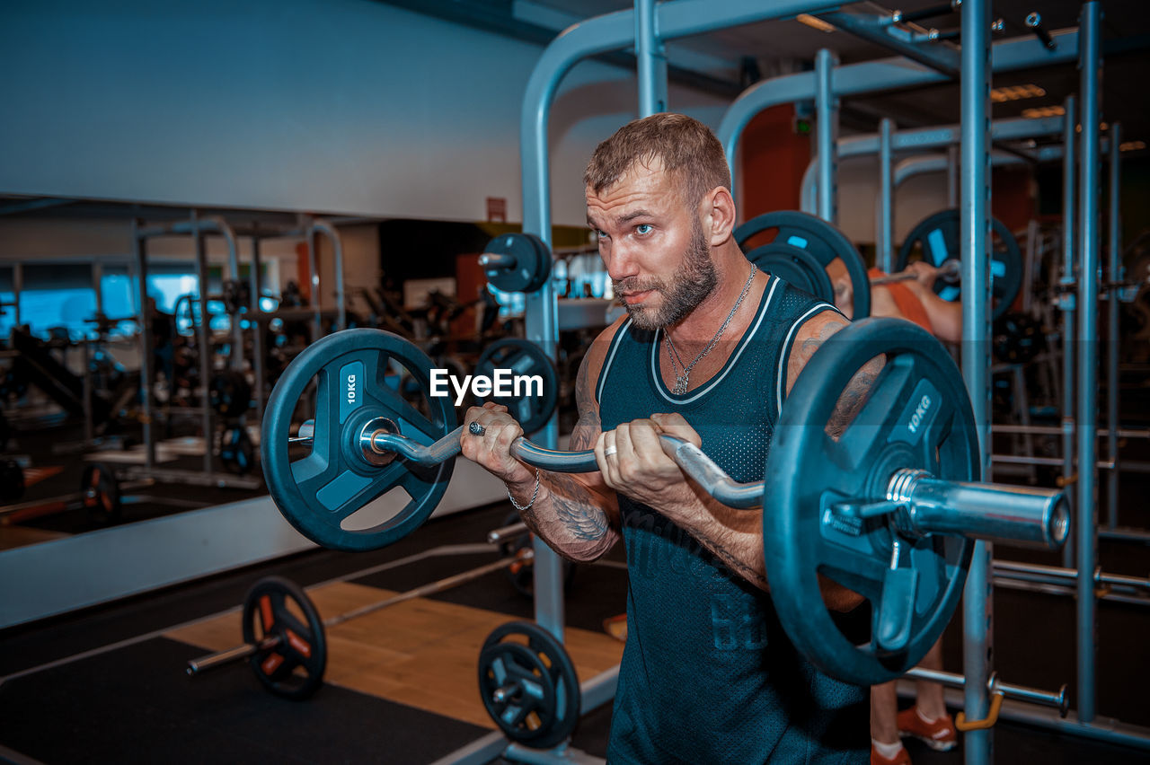 weight, muscular build, weight training, one person, strength, exercising, weights, gym, sports training, real people, men, exercise equipment, indoors, sport, lifestyles, equipment, healthy lifestyle, young adult, barbell, dumbbell, effort