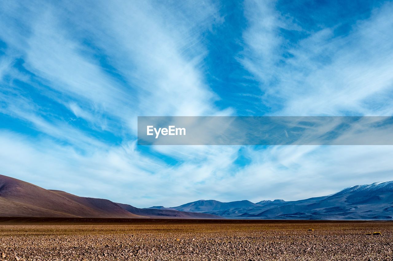 cloud - sky, sky, scenics - nature, beauty in nature, tranquil scene, landscape, environment, land, mountain, tranquility, blue, nature, day, non-urban scene, no people, field, mountain range, desert, outdoors, rural scene, arid climate