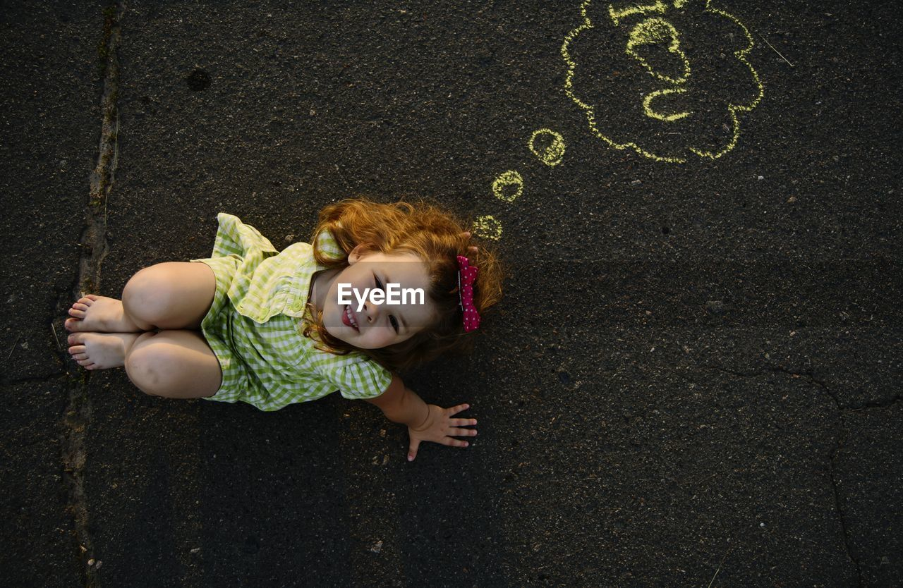 Directly Above Portrait Of Cute Girl Sitting By Chalk Drawing On Road