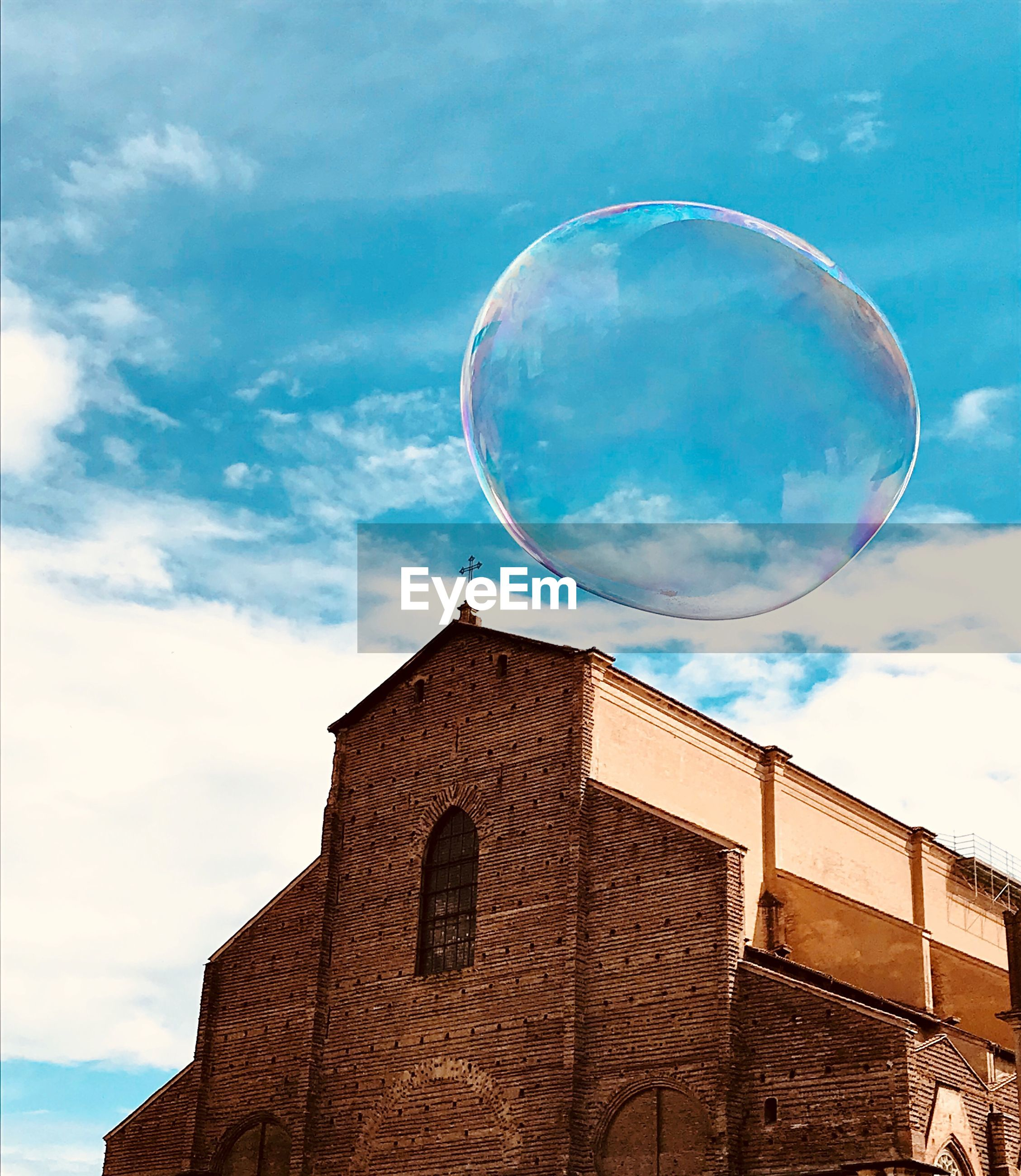 Low angle view of bubble and church against blue sky