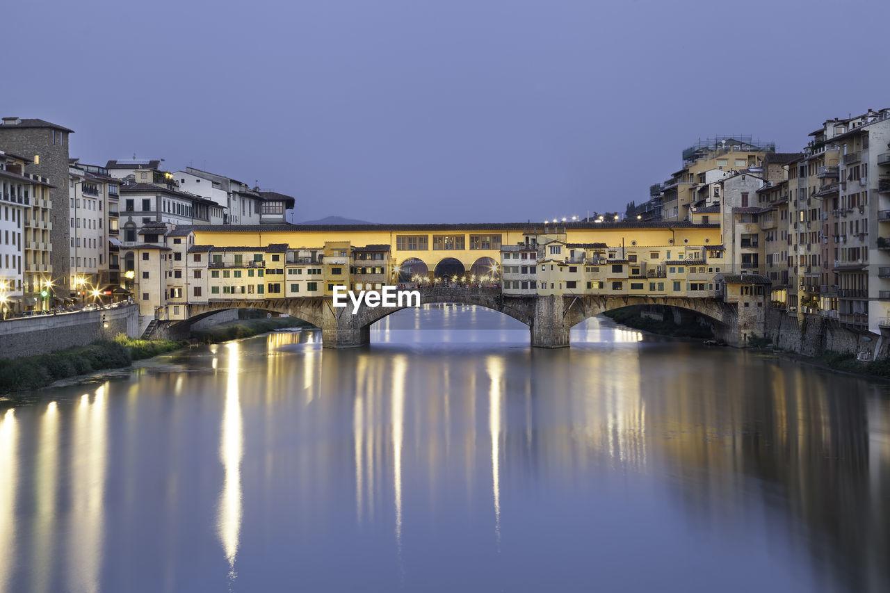 Illuminated Ponte Vecchio Over Arno River In City At Dusk