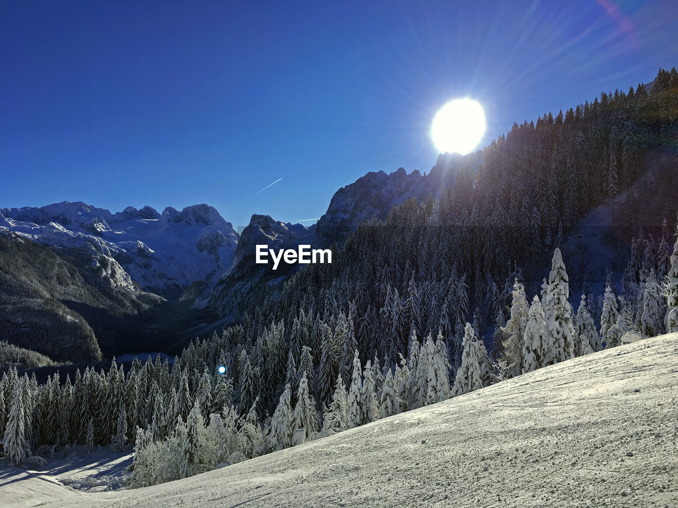 Scenic view of snowcapped mountains against bright sun