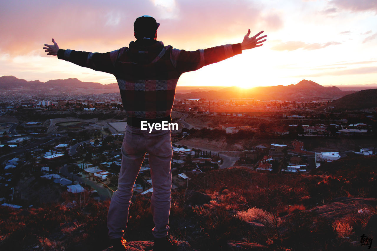 Rear View Of Man With Arms Outstretched Standing On Rock Against Cityscape Against Sky During Sunset