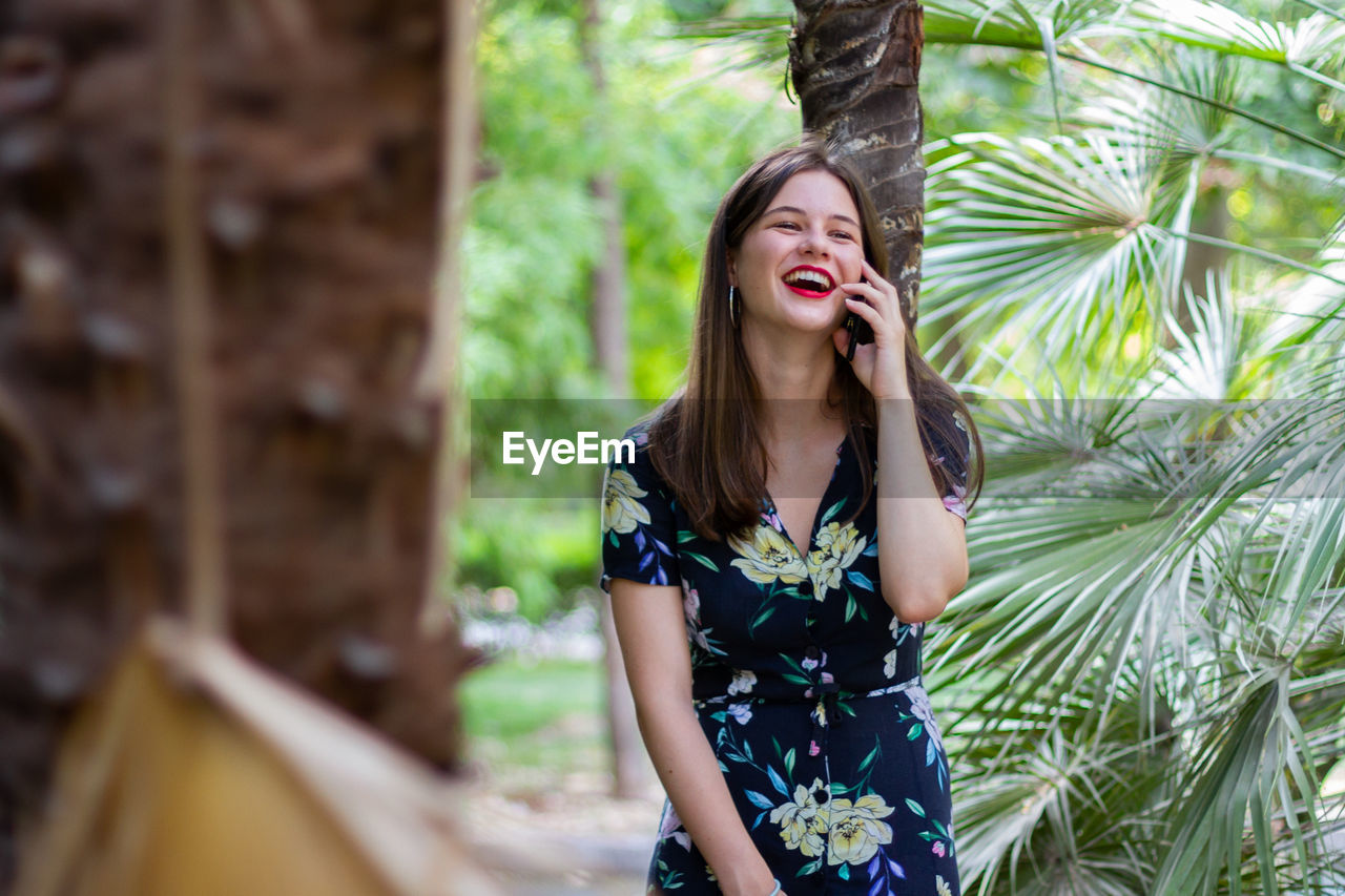 Beautiful young woman using phone while standing against tree trunk