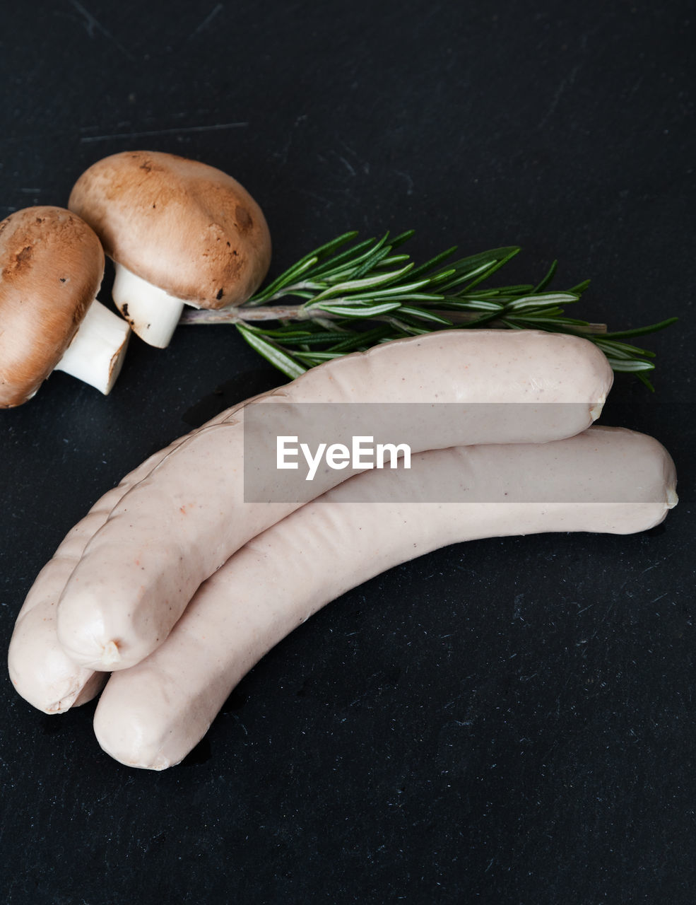 Close-up of sausage with mushroom and rosemary on table