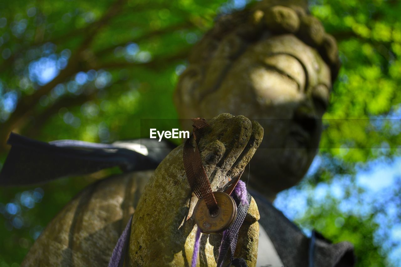 focus on foreground, no people, art and craft, close-up, tree, sculpture, representation, low angle view, day, plant, nature, statue, human representation, craft, green color, old, creativity, outdoors, metal