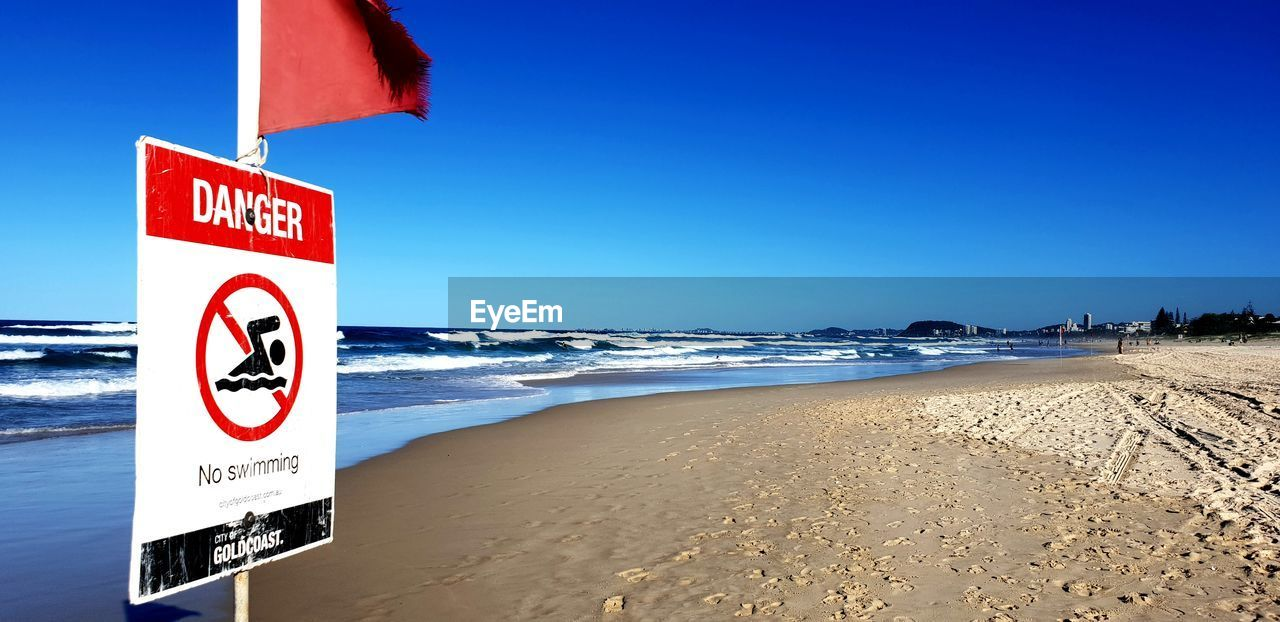 communication, water, land, sky, beach, sea, text, western script, sign, warning sign, sand, blue, nature, clear sky, day, scenics - nature, no people, guidance, information, horizon over water, outdoors