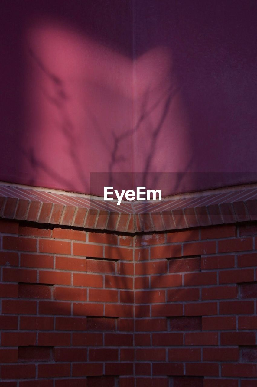 wall - building feature, brick, brick wall, architecture, built structure, wall, pink color, building exterior, no people, pattern, night, close-up, container, illuminated, red, purple, shadow