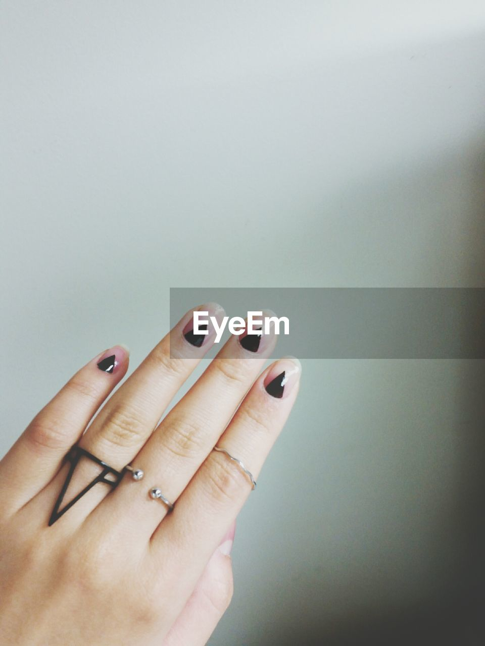 Cropped Hand Of Woman With Painted Nails Against Wall