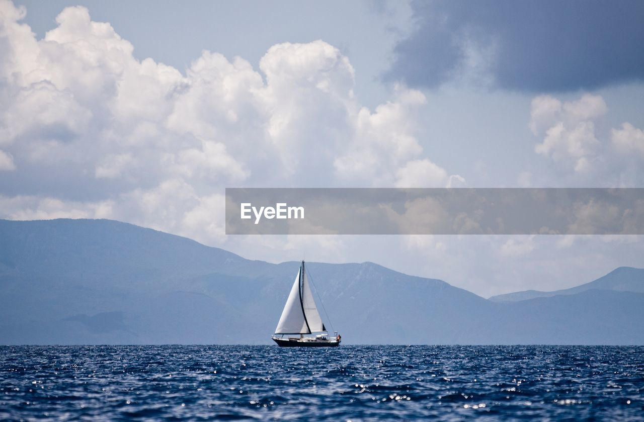 Sailboat Sailing In Sea By Mountains Against Sky