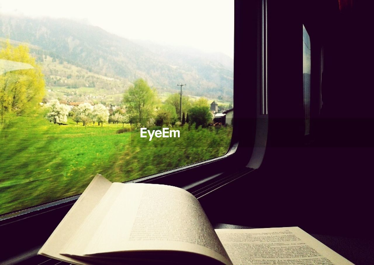 Book at train window by grassy field