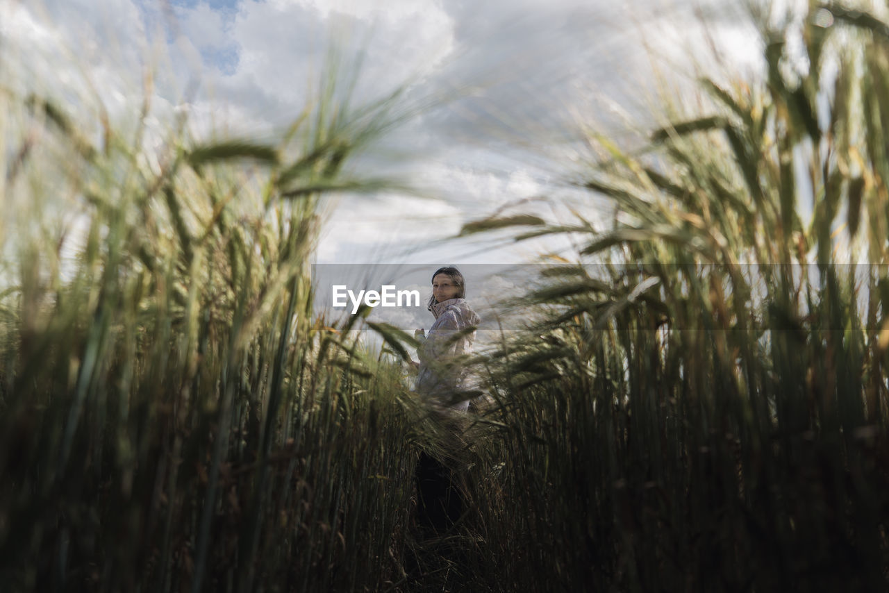 Mid Adult Woman Standing In Field Against Sky