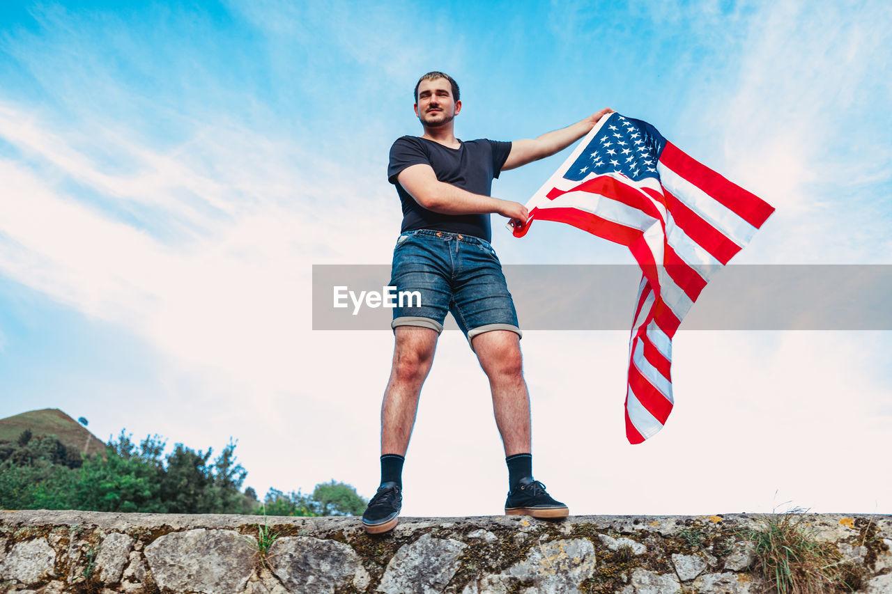 FULL LENGTH OF MAN STANDING IN FRONT OF FLAG AGAINST SKY
