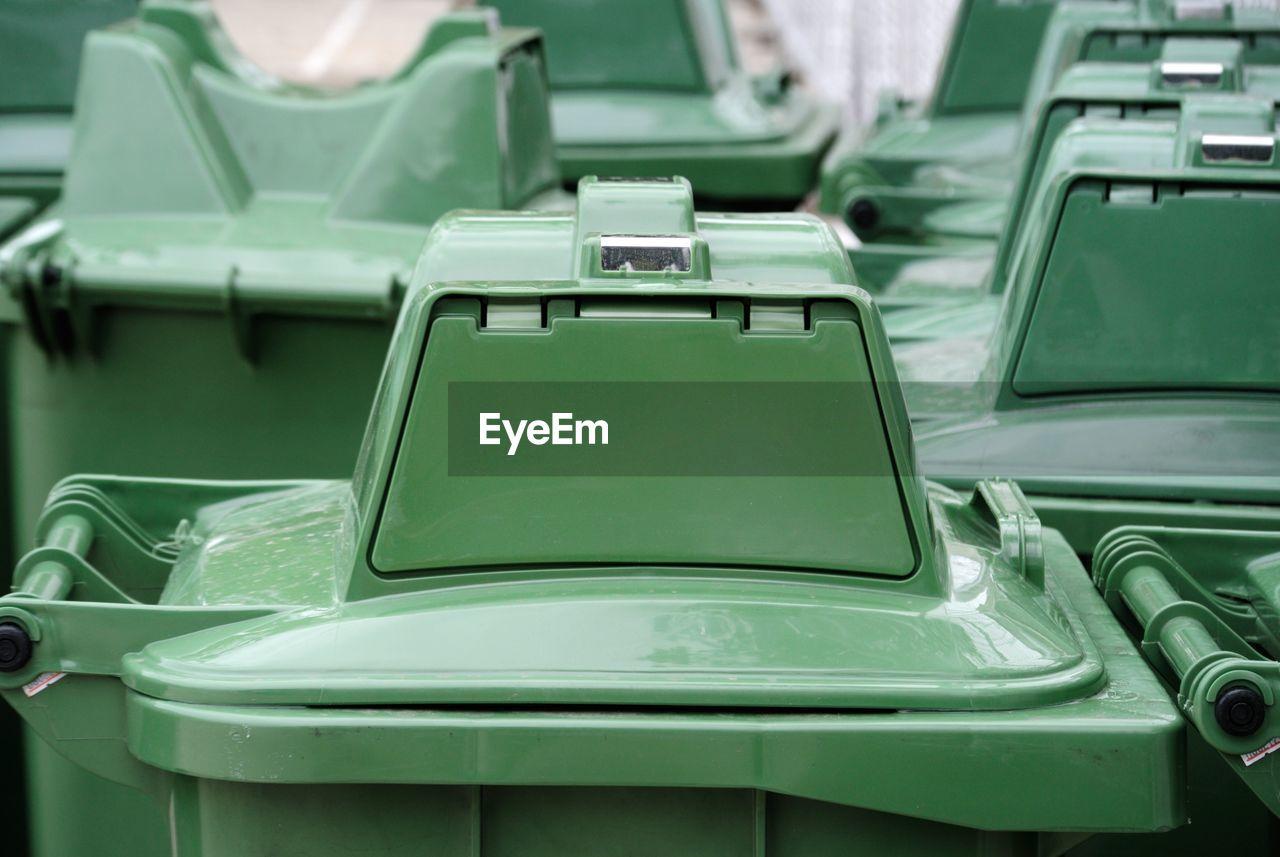 Close-Up Of Green Garbage Bins