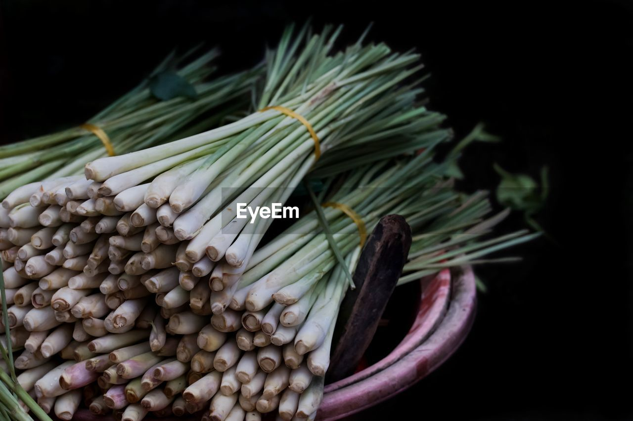 Close-Up Of Spring Onions Against Black Background