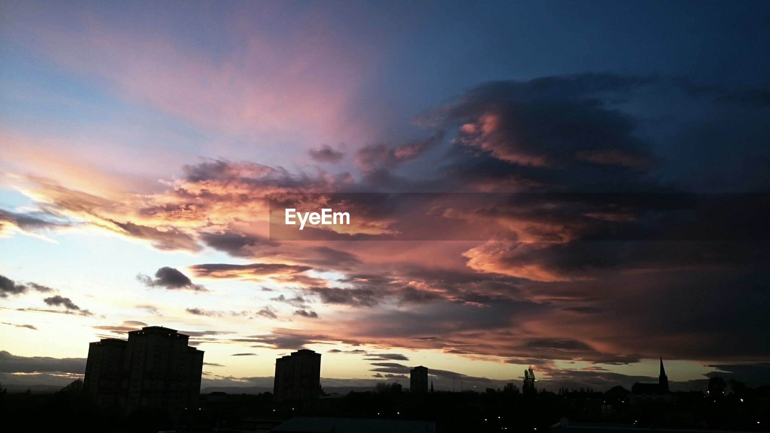 sunset, sky, cloud - sky, silhouette, building exterior, built structure, cloudy, architecture, dramatic sky, weather, cloud, beauty in nature, scenics, dusk, city, orange color, nature, overcast, low angle view, outdoors