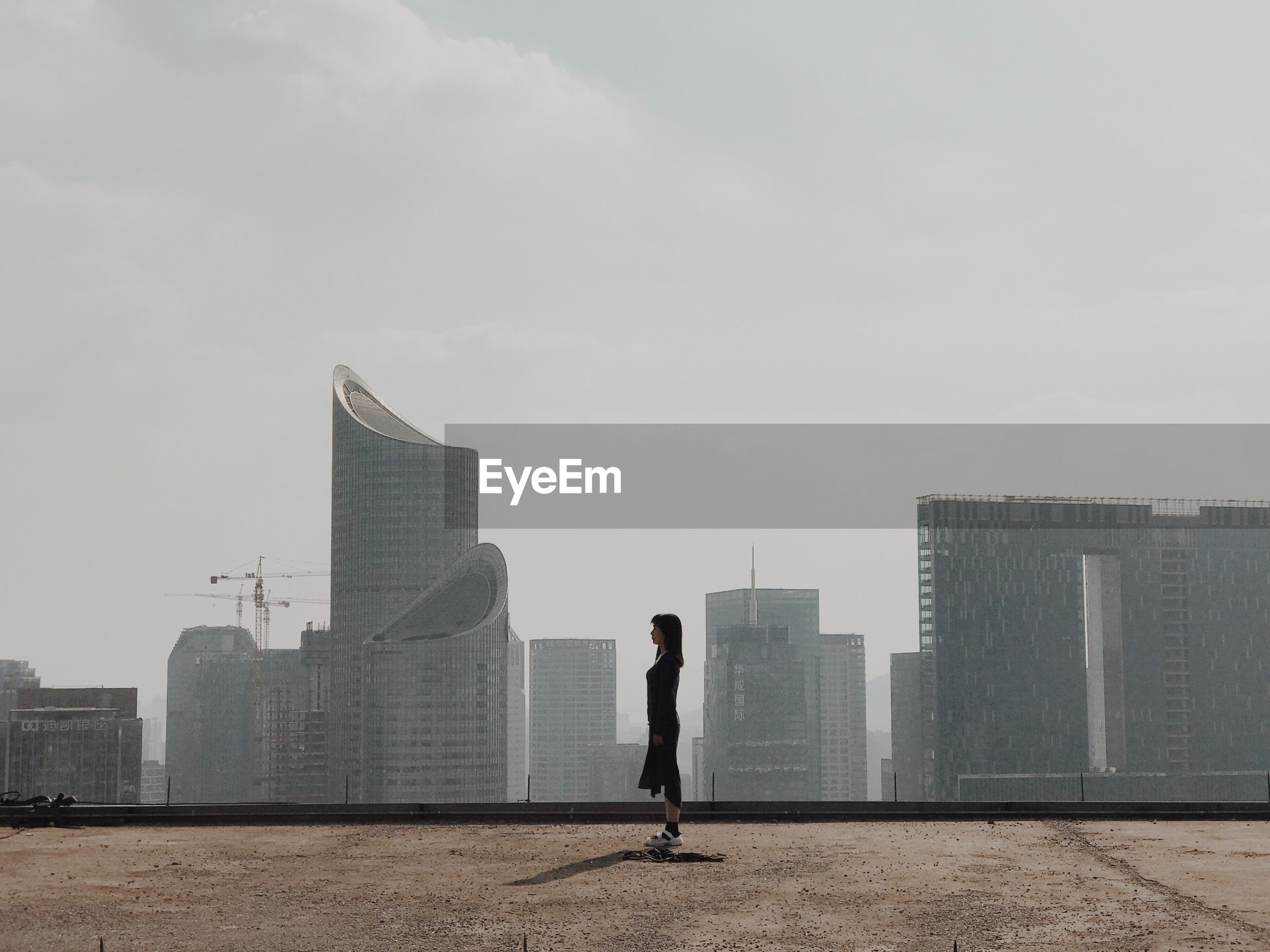 Side view of young woman standing on terrace against skyscrapers