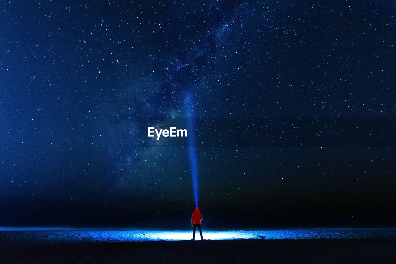 Rear View Of Person With Illuminated Flashlight Standing Against Star Field At Night