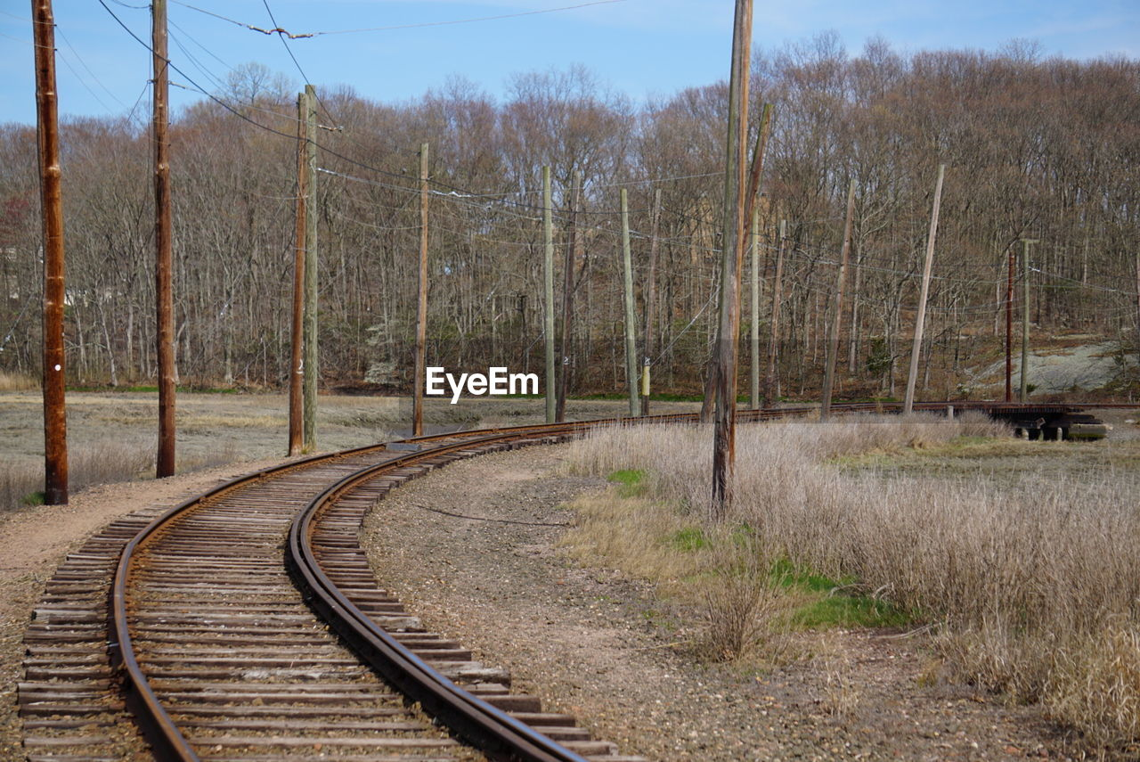 transportation, railroad track, rail transportation, tree, no people, day, the way forward, scenics, tranquil scene, outdoors, tranquility, nature, landscape, beauty in nature, curve, sky, bare tree