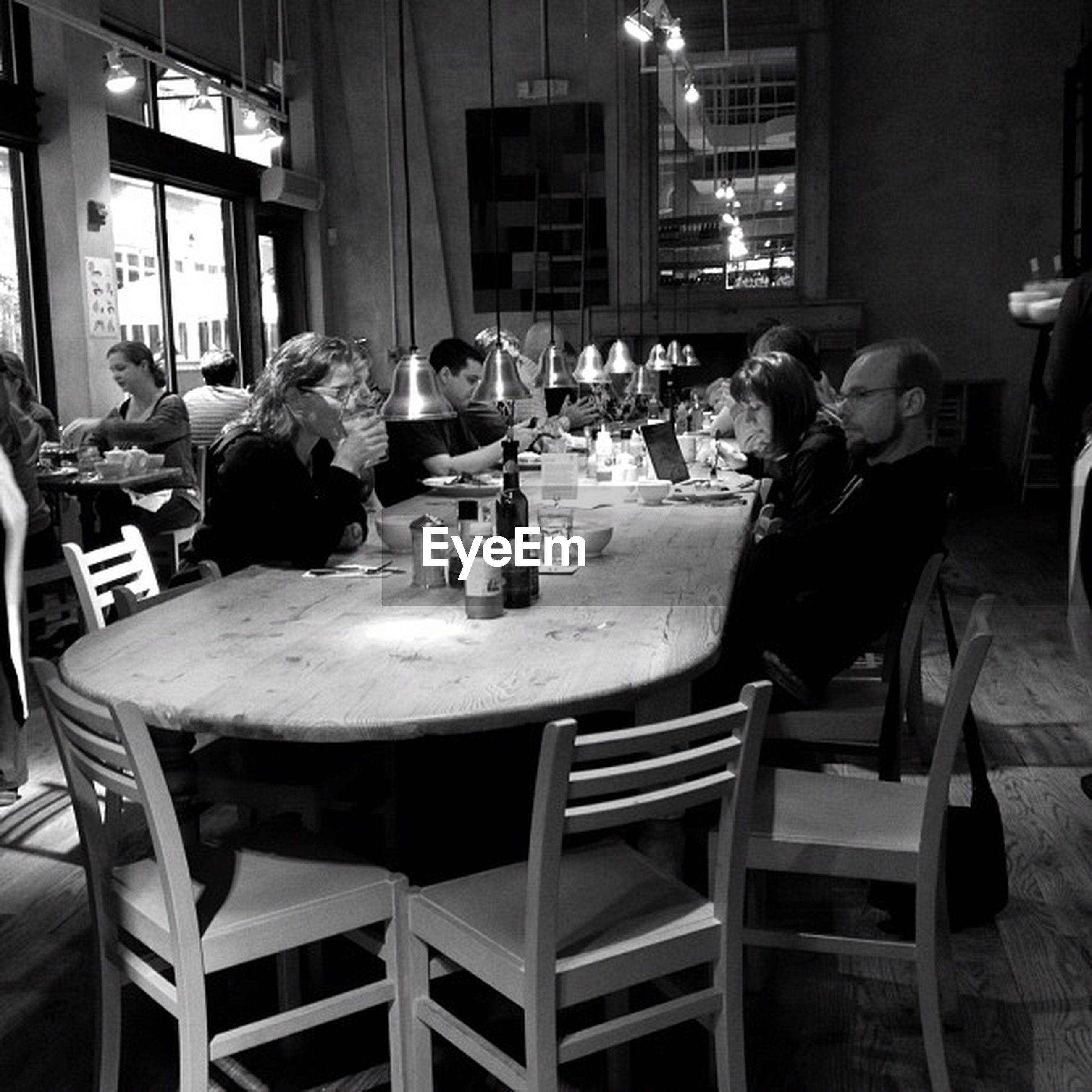 table, indoors, sitting, men, restaurant, chair, food and drink, lifestyles, food, leisure activity, person, night, built structure, occupation, architecture, sidewalk cafe, casual clothing, working