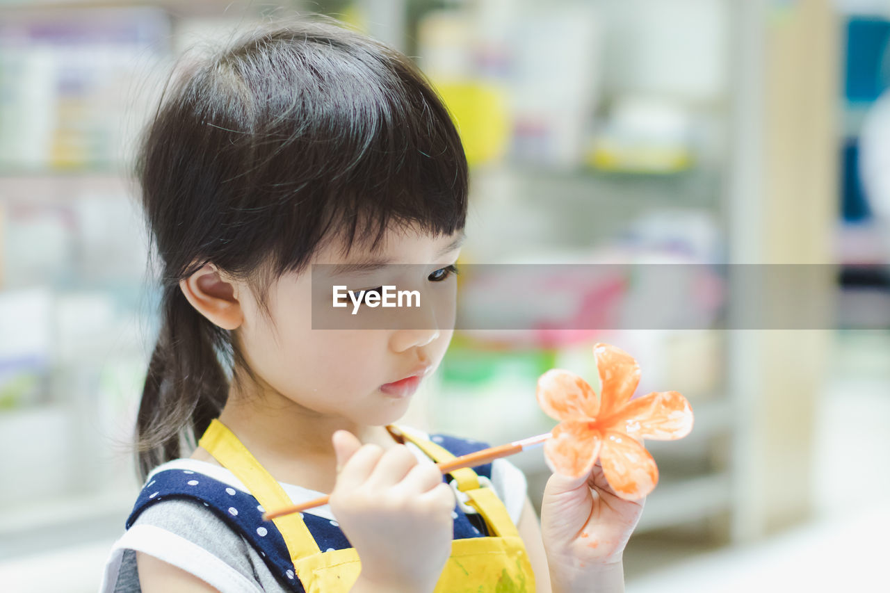 Close-Up Of Girl Painting Flower