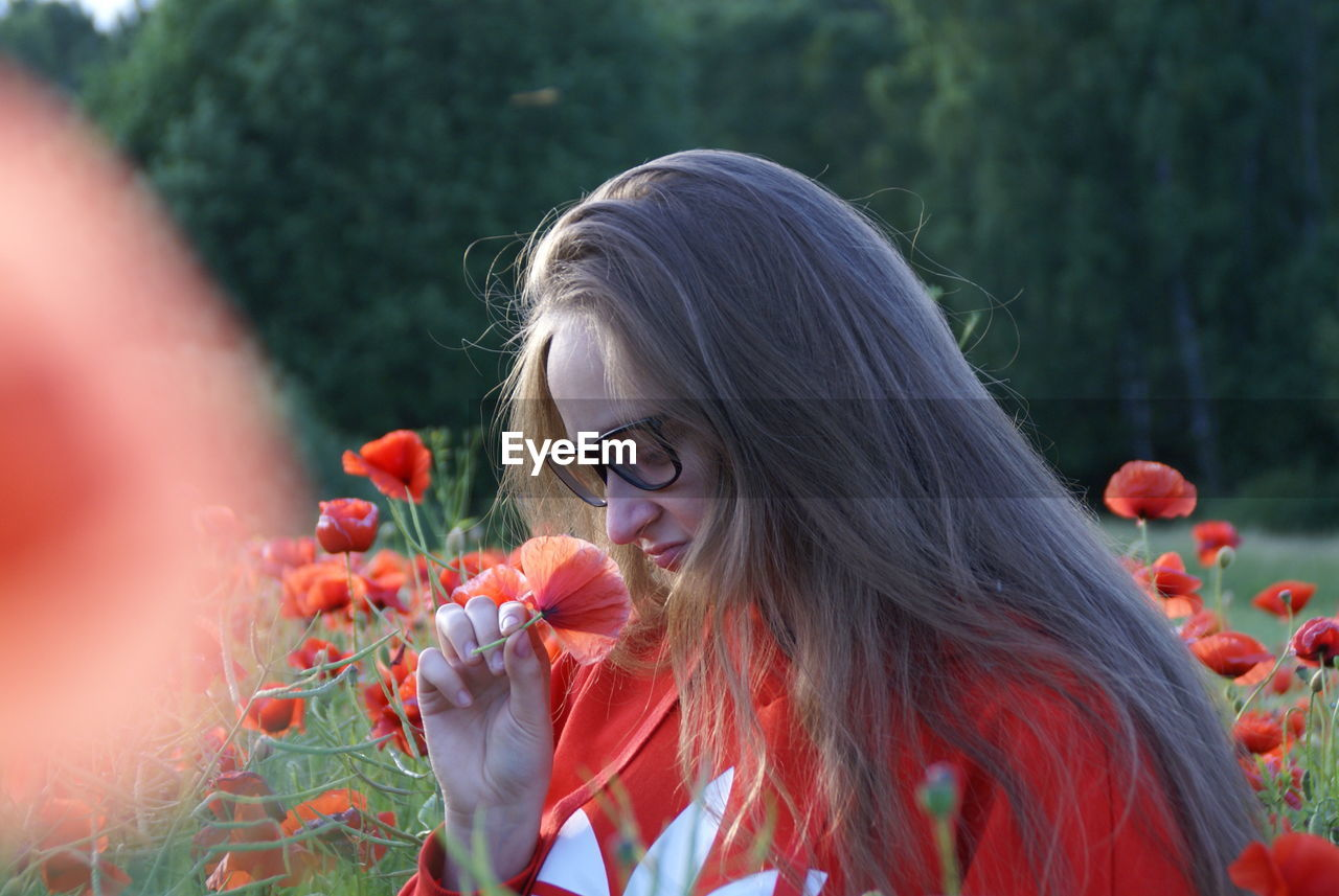 Young Woman In Eyeglasses Smelling Poppy While Sitting On Field