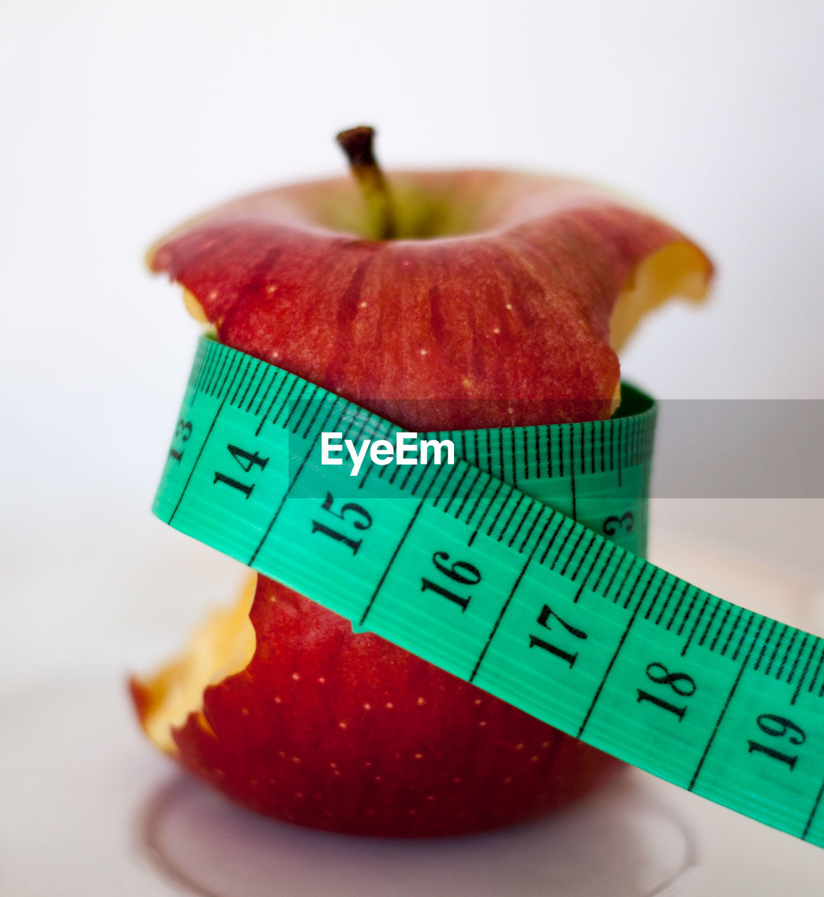 Close-up of bitten apple with tape measure against white background