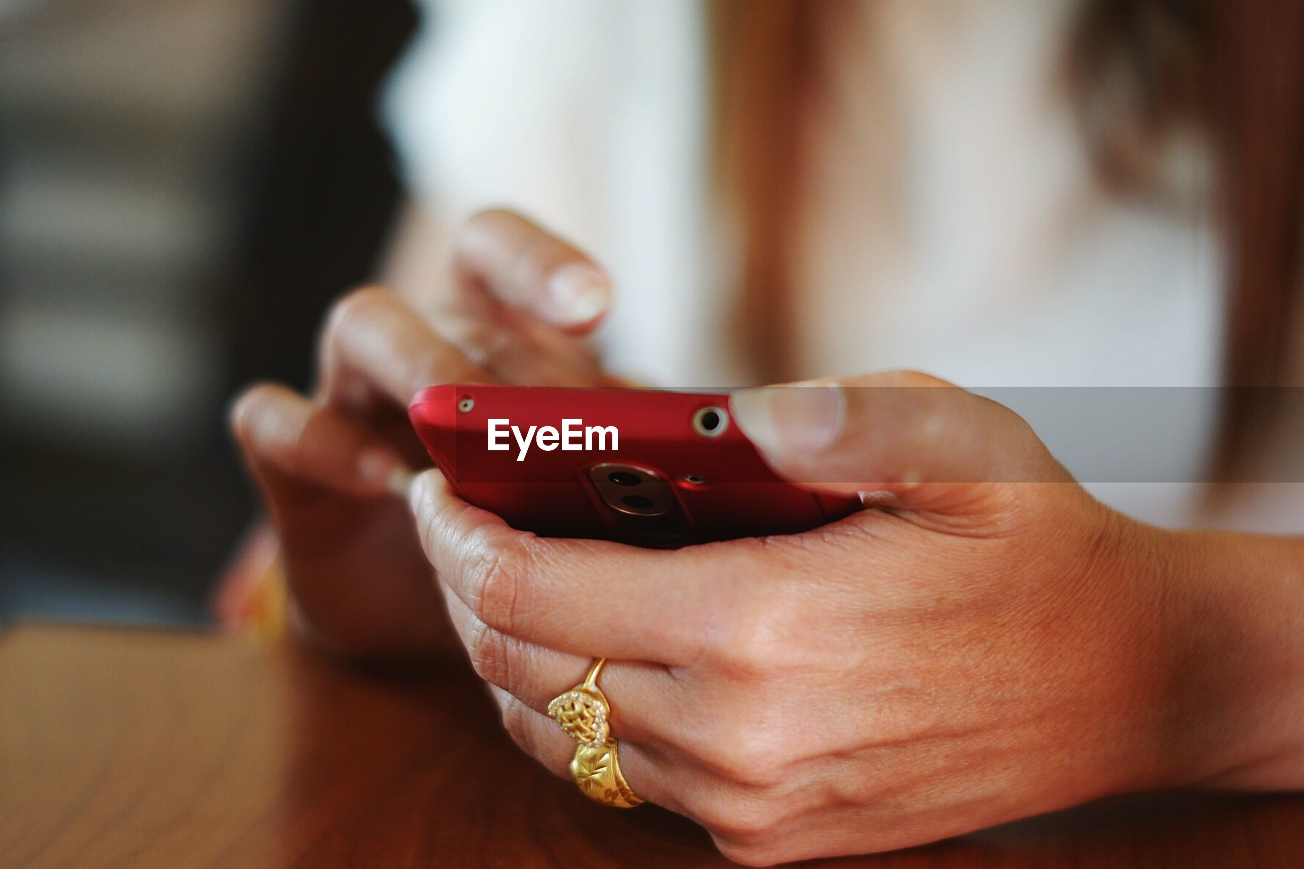 Close-up midsection of woman using phone on desk