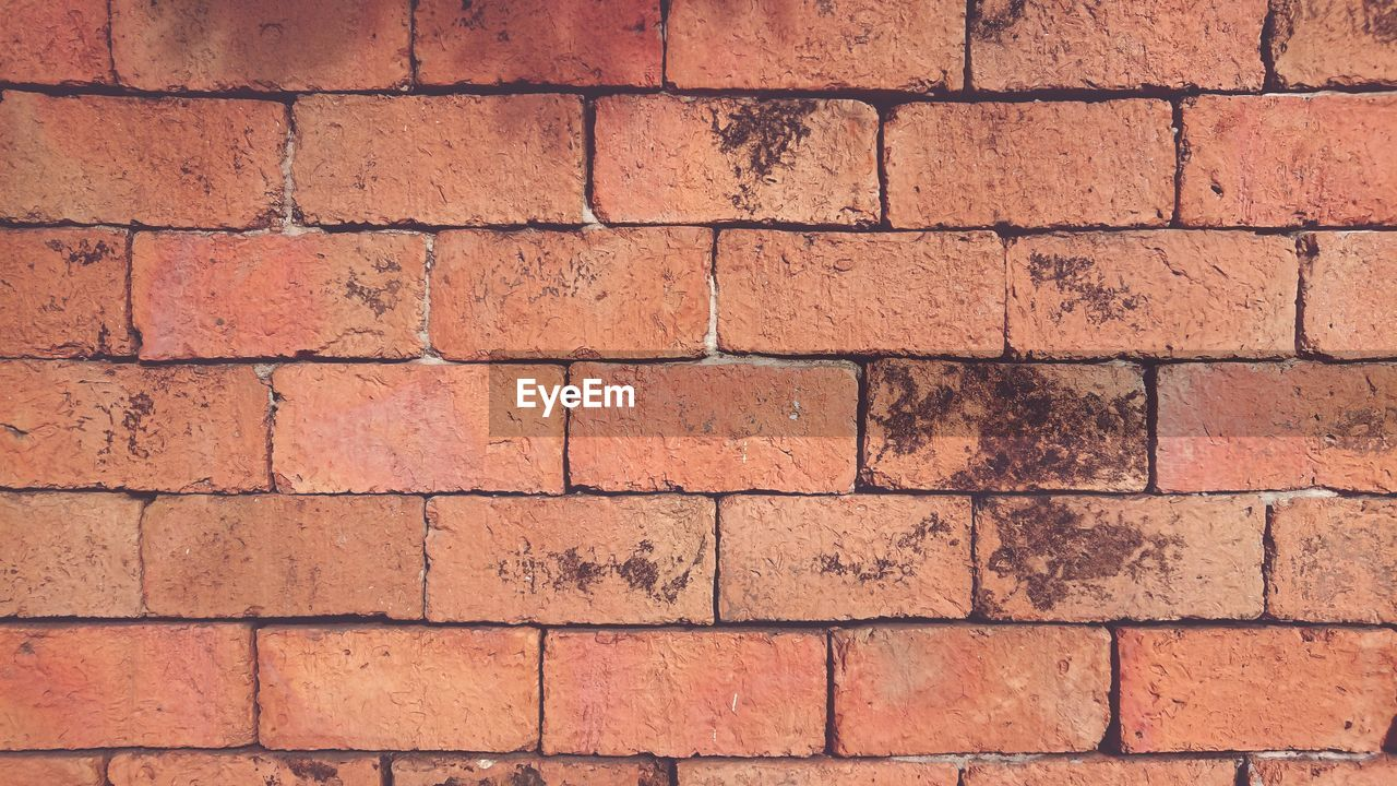 FULL FRAME SHOT OF BRICK WALL WITH RED STONE