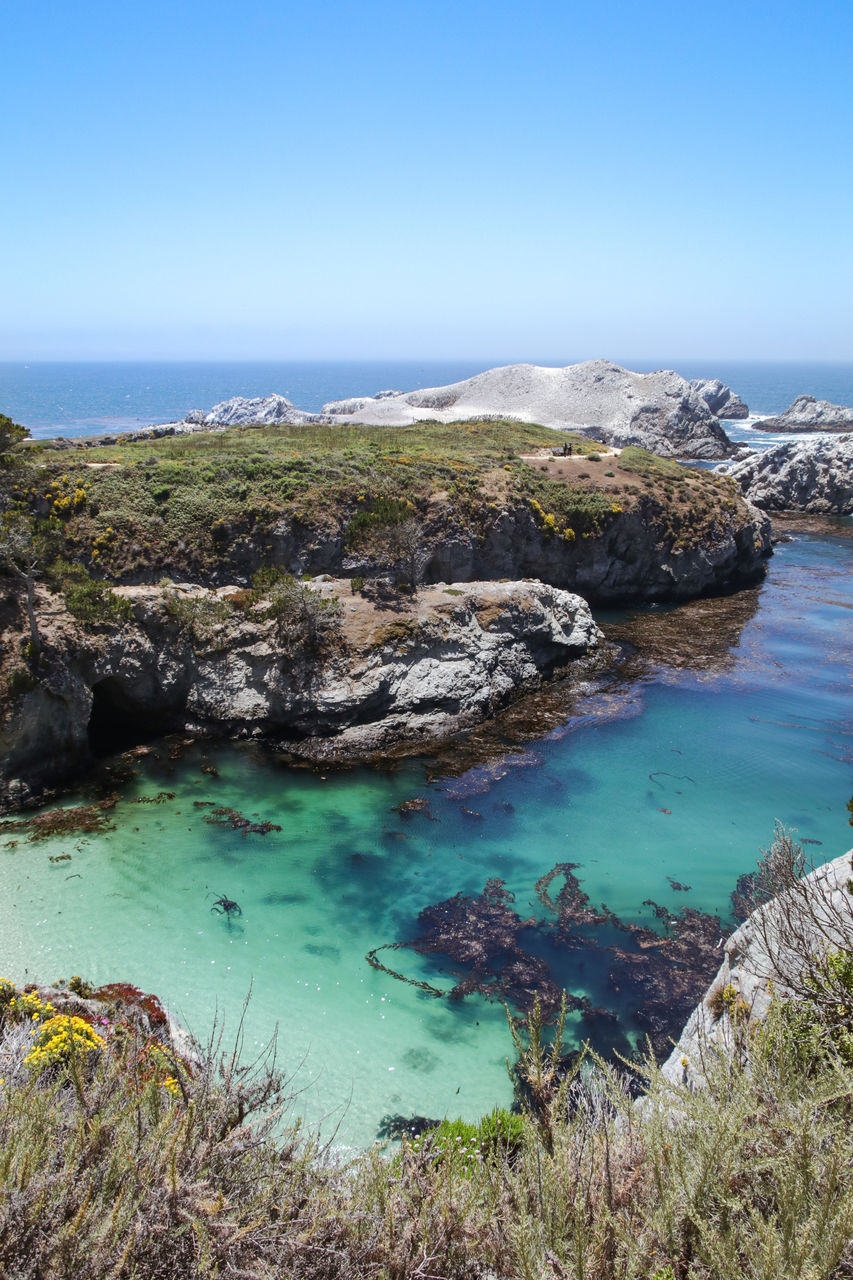 water, sea, scenics - nature, sky, tranquil scene, rock, solid, beauty in nature, rock - object, tranquility, blue, land, nature, day, clear sky, no people, rock formation, beach, high angle view, horizon over water, outdoors, turquoise colored, rocky coastline, eroded