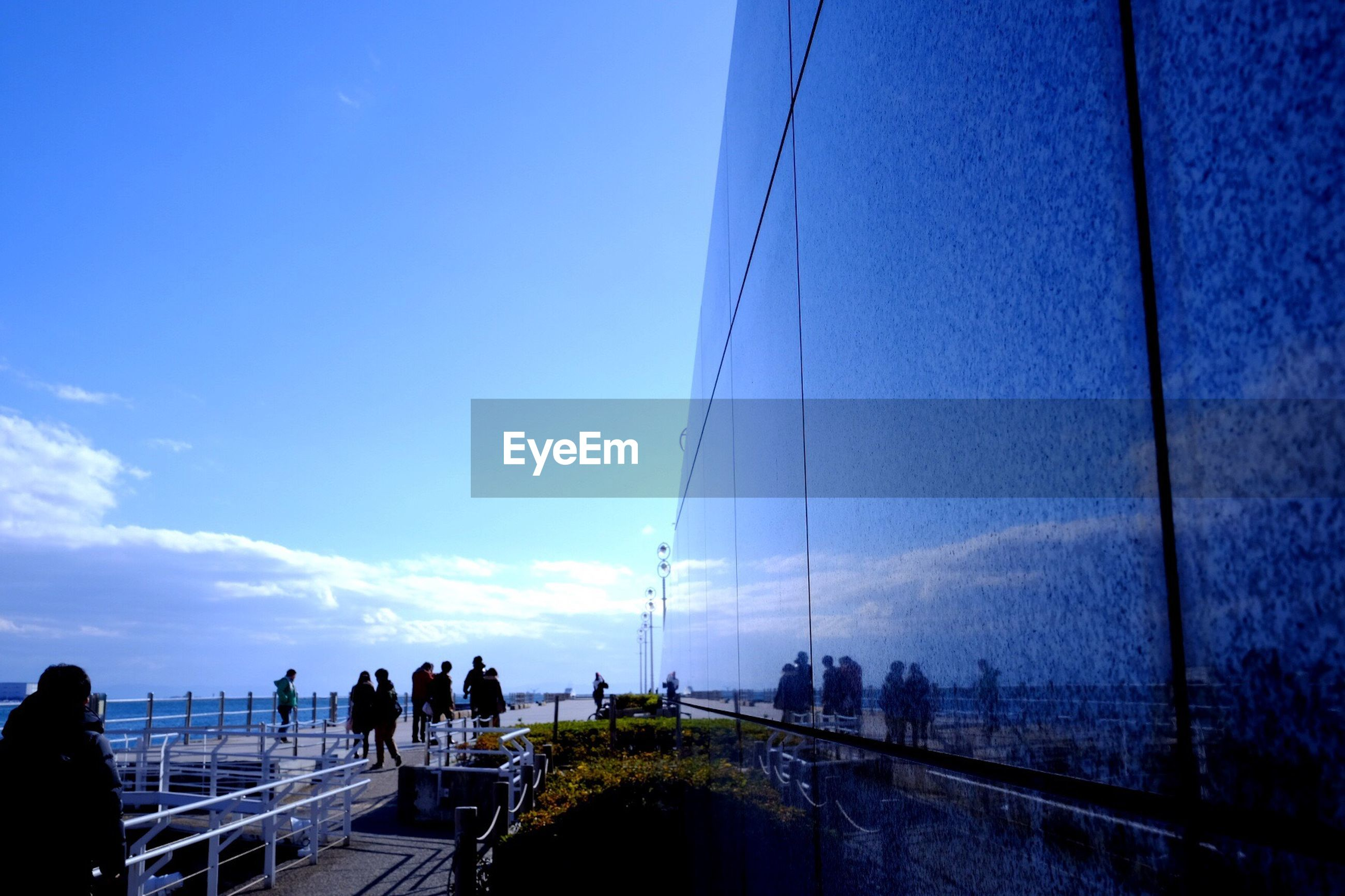 sky, silhouette, men, transportation, lifestyles, connection, leisure activity, water, blue, person, walking, large group of people, road, sea, medium group of people, nature, railing, bridge - man made structure, outdoors