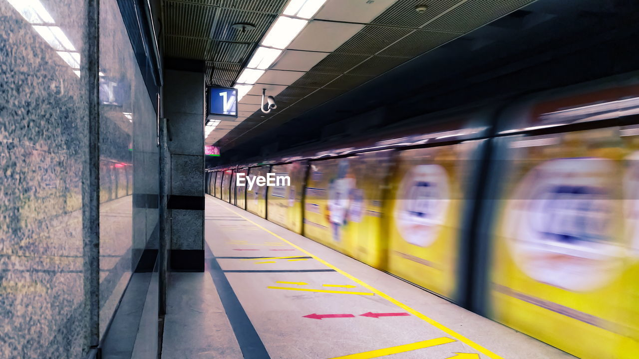 public transportation, rail transportation, train, transportation, railroad station platform, railroad station, mode of transportation, architecture, train - vehicle, blurred motion, motion, indoors, no people, built structure, passenger train, travel, subway, subway train, track, ceiling