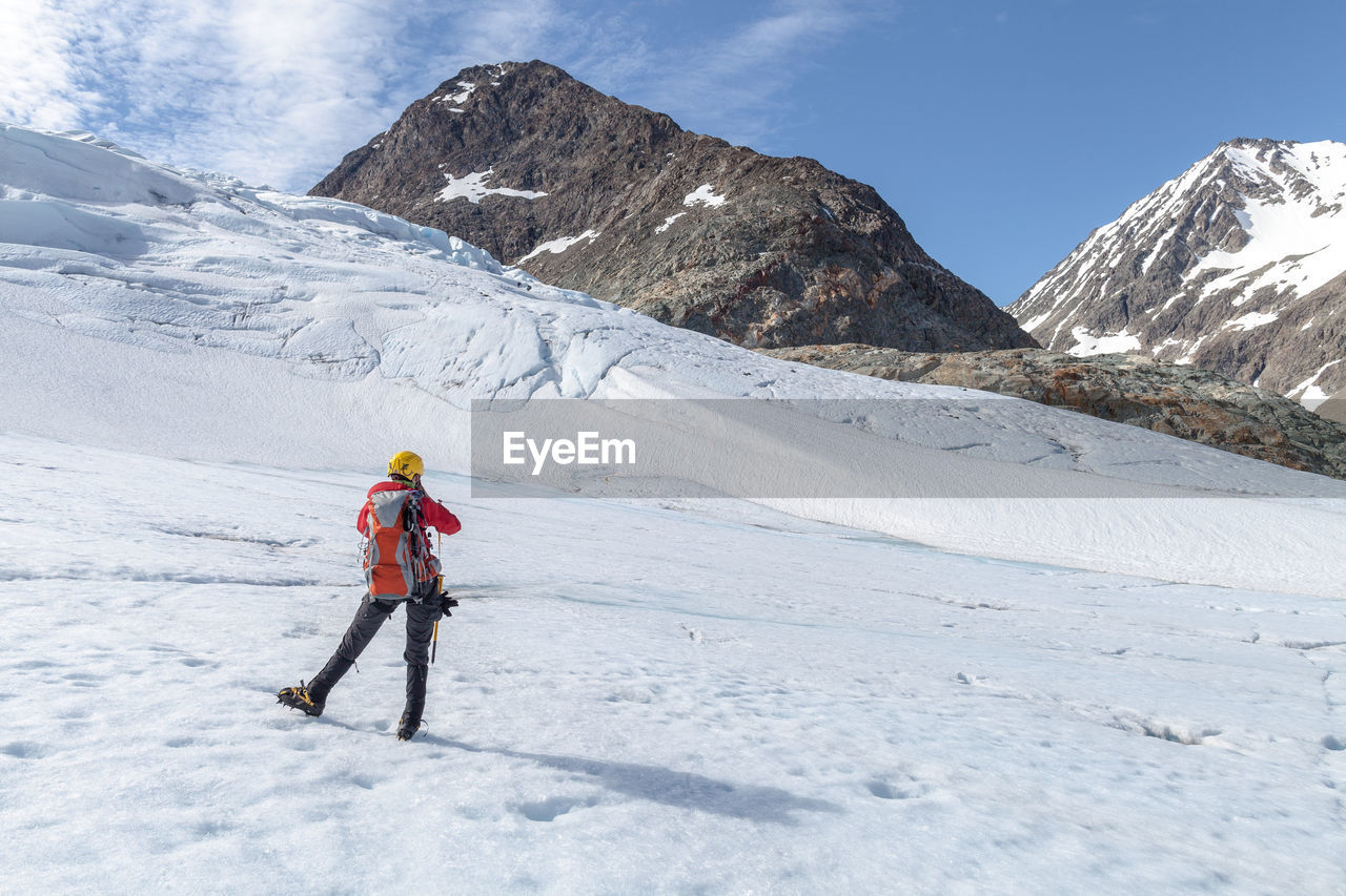 Rear View Of Hiker Standing On Snow Covered Field By Rocky Mountains Against Sky