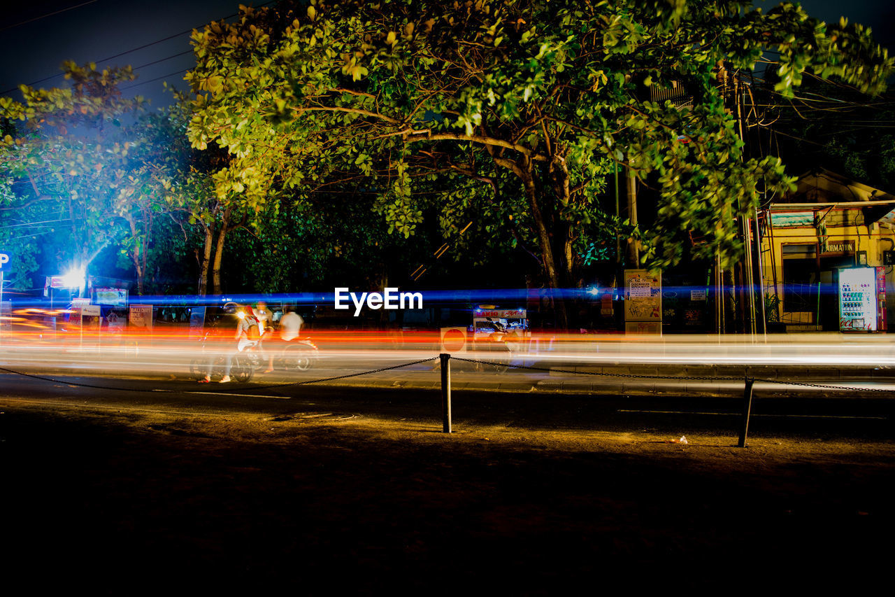 night, long exposure, tree, motion, illuminated, light trail, plant, blurred motion, speed, city, transportation, street, architecture, road, nature, outdoors, built structure, mode of transportation, incidental people, building exterior