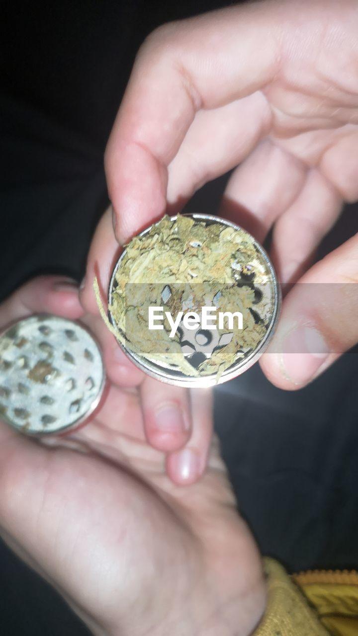 Close-Up Of Hands Holding Marijuana In Grinder
