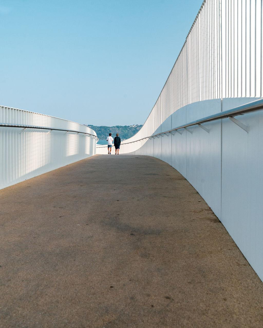 Rear View Of People Walking On Bridge Against Sky