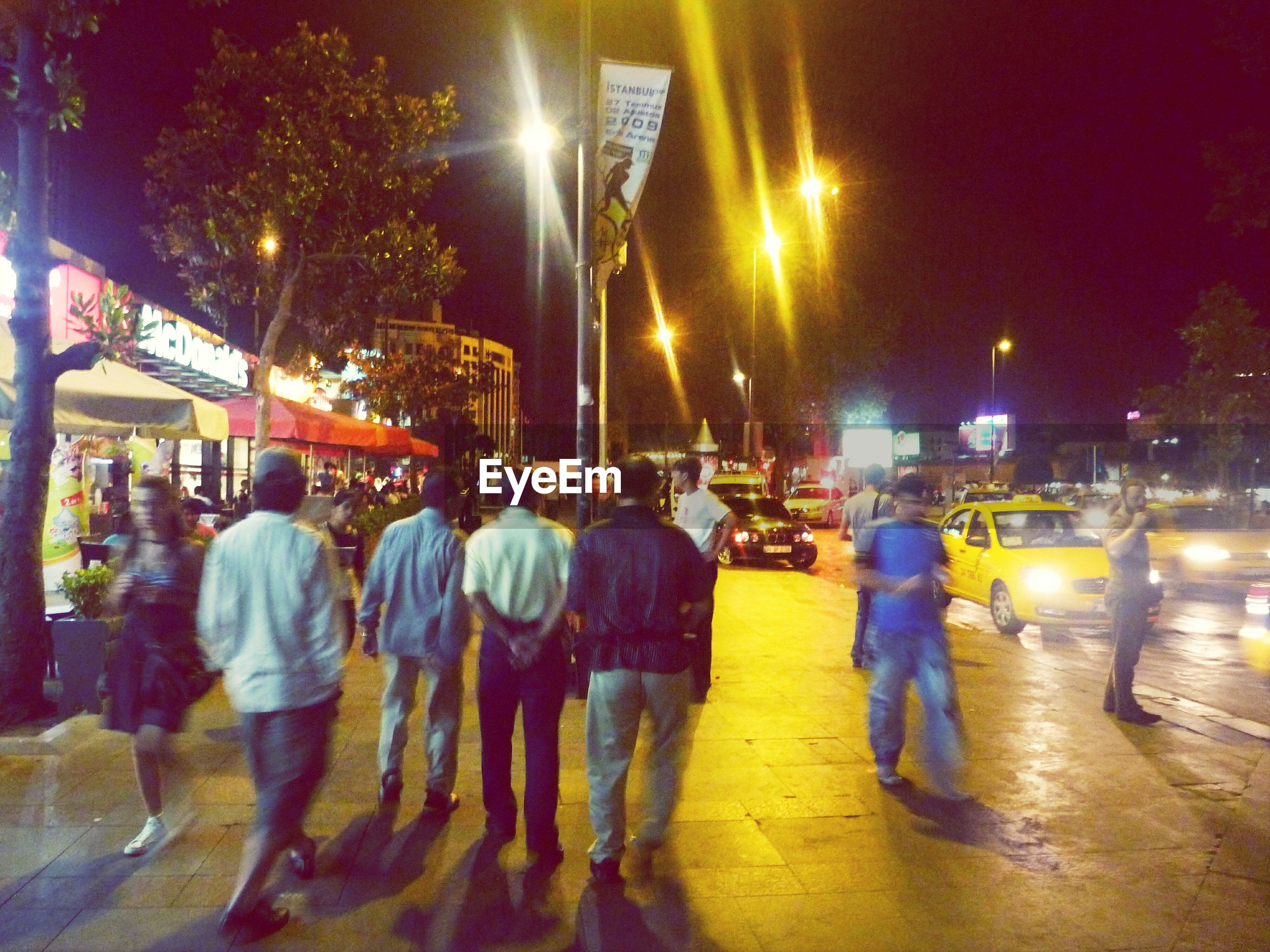 illuminated, night, street, city, building exterior, city life, transportation, men, street light, built structure, lighting equipment, architecture, walking, city street, mode of transport, person, lifestyles, incidental people, large group of people