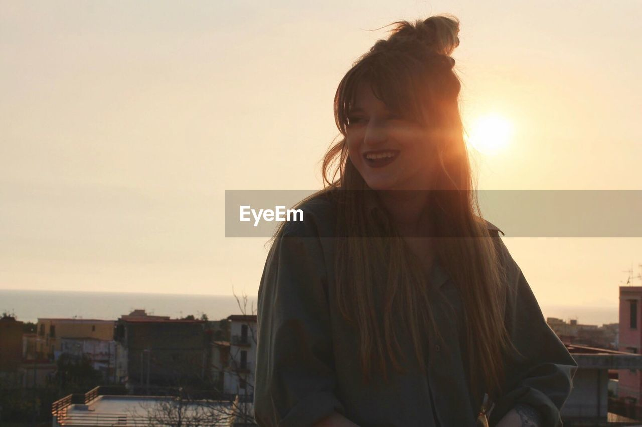 Happy woman looking away against sky during sunset in city