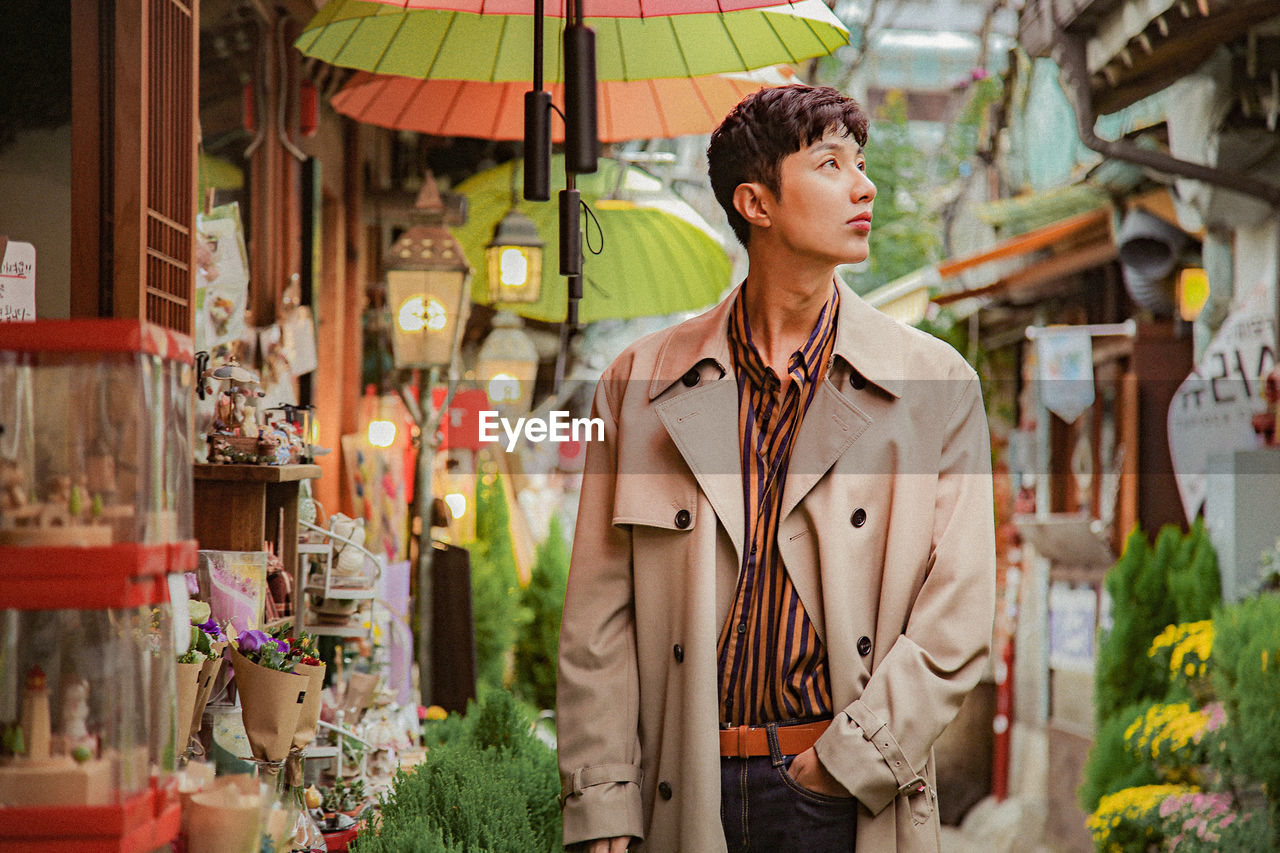 Thoughtful man looking away while standing in market