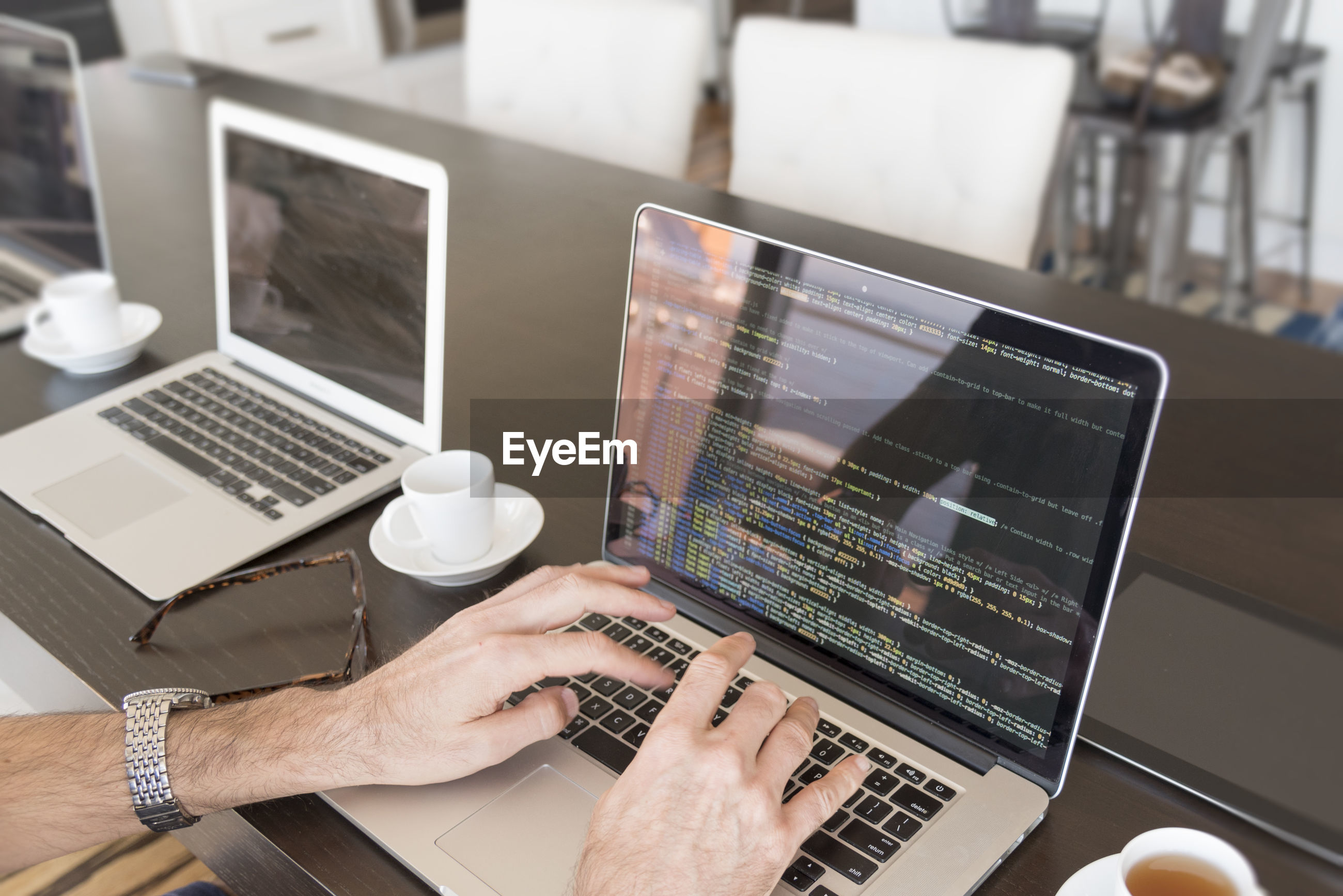 Cropped hands of businessman using laptop in office
