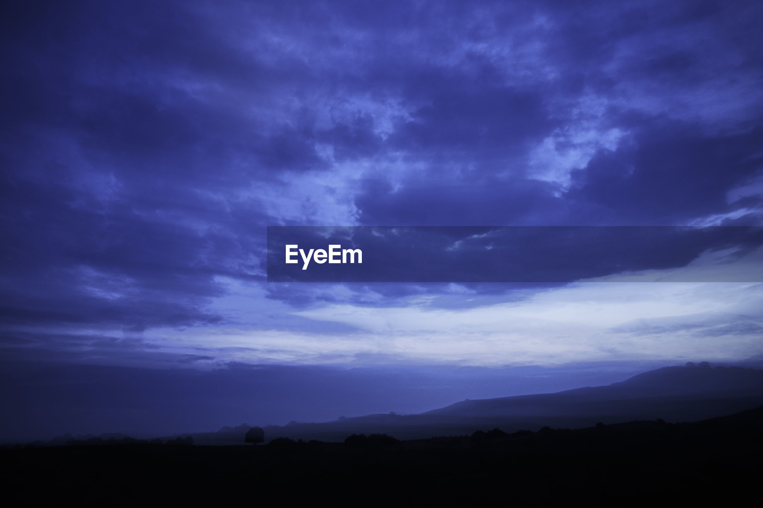 Foggy landscape in the night, clouds in the sky, blue, tree silhouette and hills